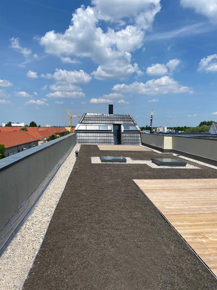 Gestaltete Dachterrasse mit COMFORT und ACCESS Oberlichtern sowie einer Lichtband-Verglasung im Dach
